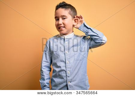 Young little boy kid wearing elegant shirt standing over yellow isolated background smiling with hand over ear listening an hearing to rumor or gossip. Deafness concept.