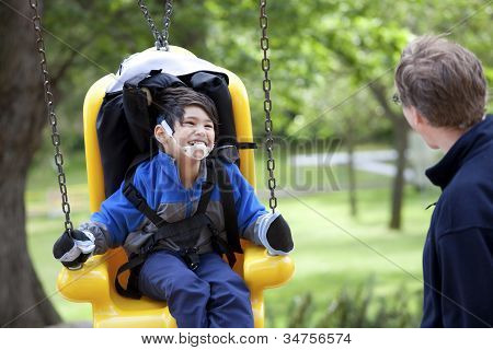 Father Pushing Disabled Son  On Handicap Swing