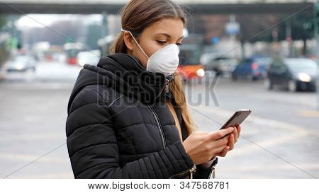 COVID-19 Pandemic Coronavirus 2019-nCoV. Young woman using smart phone in the city wearing face mask because of air pollution, particulates or flu virus, influenza, coronavirus