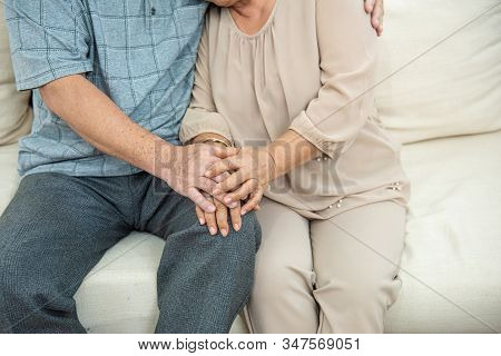 Cropped Photo Of Hands Of Cute Elder Senior Asian Couple Holding Hands With Love On Sofa.old People