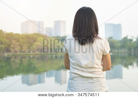 Back Part Of Young Asian Woman In Casual White Shirt With Reflex Of Water And Building.