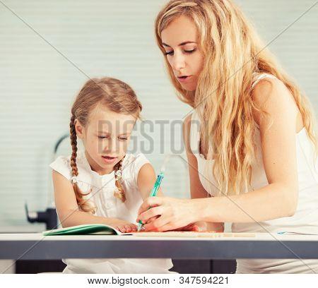 Parent teaches a child to write. Mom helping her daughter do homework
