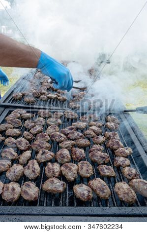 Grilled Meatballs At Picnic In Rotisserie With Sterilized Glove