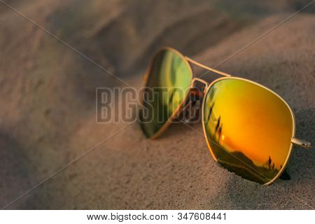 Reflecting Glasses Close Up On Beach Sand With Sunset And People Reflection. Mirrored Glasses On San