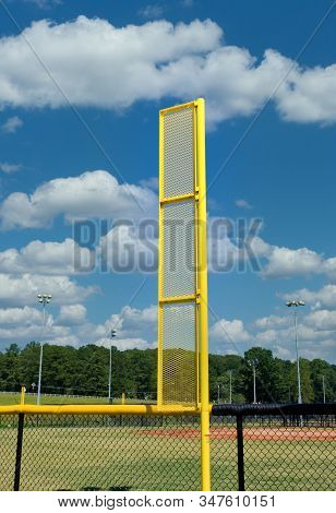 A Bright Yellow Foul Ball Pole In A Baseball Field Against Blue Sky