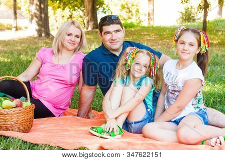 Happy Two Parent Family With Two Daughters On Orange Picnic Blanket In The Park