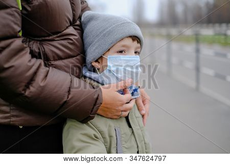 The Kid Is Standing Near Mom In A Medical Mask. Protection Against Chinese Coronavirus. European Tou