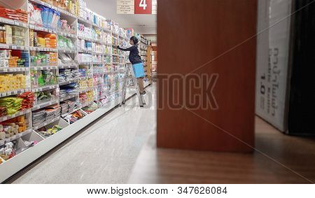 Bangkok, Thailand - January 26: Supermarket Employee Climbs On A Ladder To Organize Product Shelf In