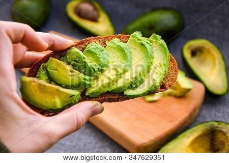 Healthy Breakfast. Female Hand Holding Avocado Toast, Green Organic Avocado