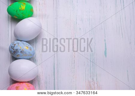 Easter Background. Easter Multi-colored Eggs With A Side Of A White Wooden Background And A Place Fo