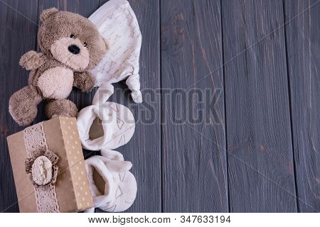 Birthday Baby Card, Newborn Card With Place For Inscription. Toy Bear, Booties On A Gray Wooden Back