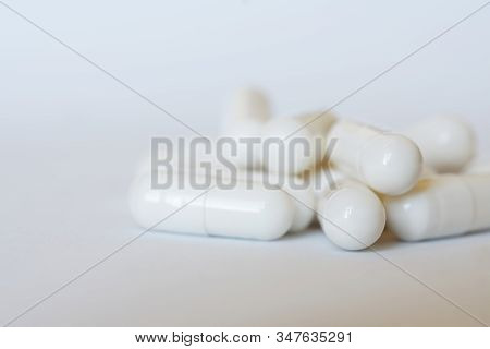 White Pill Capsules On A Light Background. Macro. Shallow Depth Of Field. Health And Medicine. Dayli