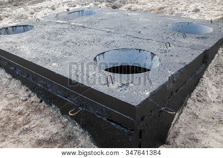 Manhole In The Concrete Block Painted With Black Coal Tar. Construction Site.