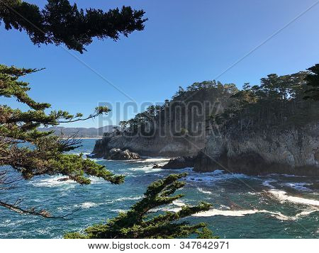 Waves Crash Against Cliffs With Trees In Big Sur, California