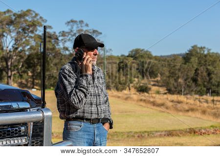 Man On Mobile Phone Looking Away Next To Truck With Antennas