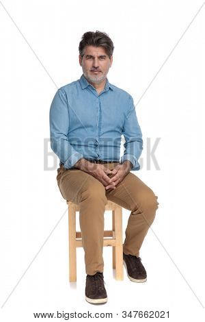 Bothered casual man looking forward and holding his hands together while sitting on a chair on white studio background