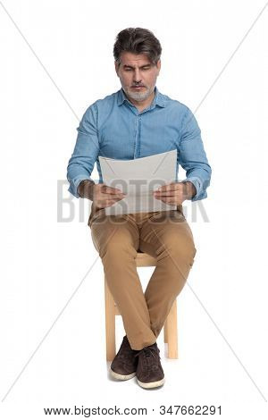 Bothered casual man reading a newspaper and frowning while sitting on a chair on white studio background