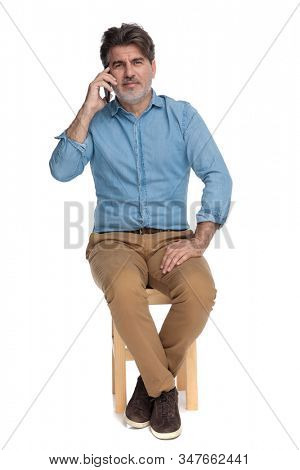 Bothered casual man talking on his phone and disagreeing while sitting on a chair on white studio background