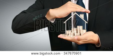 Growing Coins House On Stack Coins In Hand. Concept Of Investment Propert