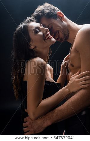 Side View Of Smiling Muscular Man Hugging Sexy Woman In Corset Isolated On Black
