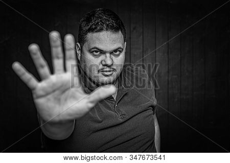 Black And White Latino Man Using An Open Hand To Make A Stop Gesture