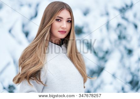 Fashion Young Woman In The Winter Forest. Young Elegant Model In Trendy White Coat In Nature. Blonde