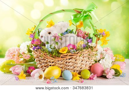 Easter composition with little white bunny in basket, spring flowers and colorful Easter eggs . Easter Card with copy space.