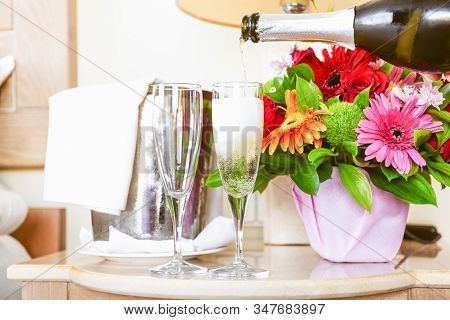 Pouring Champagne Into Glasses In The Upscale Hotel Room. Dating, Romance, Honeymoon, Valentine, Get