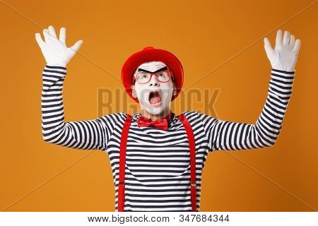 Surprised mime in red hat and in vest with hands up on orange background