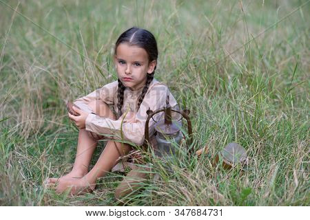 Pretty little girl with long pigtails and beautiful dirty face in summer forest and meadow holding vintage flask. Orphan, child of war, poverty, hunger, famine, poor destitute kid.