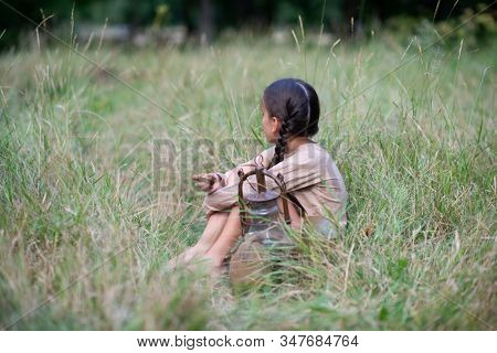 Pretty little girl with long pigtails sitting at summer meadow with vintage paraffin stove and eating stale bread. Orphan, child of war, poverty, hunger, famine, poor destitute kid.