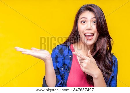 Beautiful Young Asian Woman Pointing Finger To Copy Space. Attractive Beautiful Girl Show Product Th