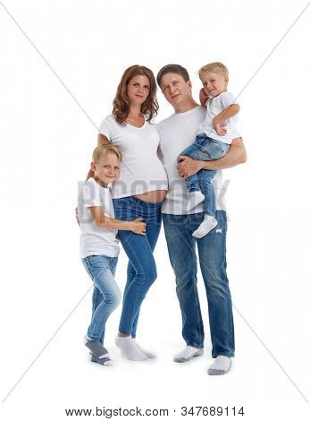 Happy parents: pregnant mother and father with lovely two sons are stand  and smiling, isolated on a white background. Happy friendly family. Concept of people and family
