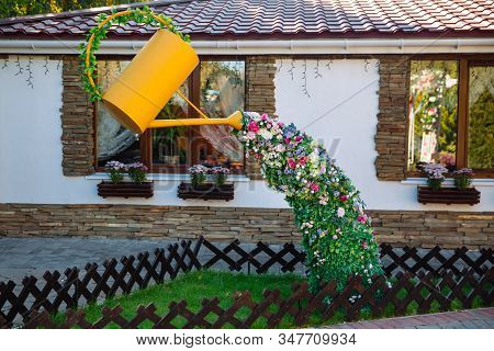 Flowerbed Of Flowers. Unusual Flowerbed, Growing Flowers Spill Out Of A Watering Can.