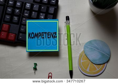 Kompetenz Write On A Sticky Note Isolated On Office Desk. German Language It Means Competence
