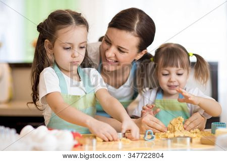 Mom With Her Little Kids Daughters Are Cooking Holiday Pie In The Kitchen