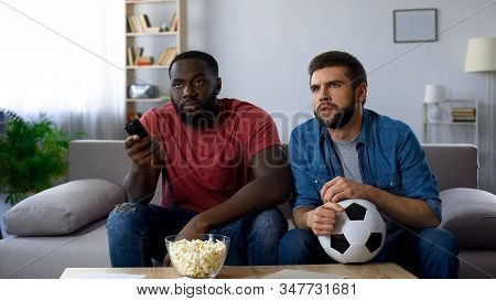 Male Friends Watching American Football Match, Trying To Understand Rules