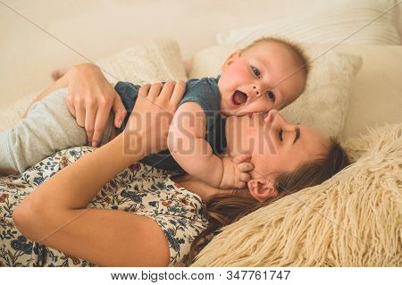 Love And Family. Home Portrait Of A Baby Boy With Mother On The Bed. Mom Play And Kissing Her Child.