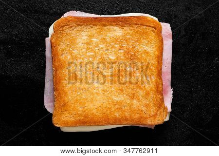 Classic Cheese And Ham Toasted Sandwich Isolated On Black Cast Iron Griddle. Top View.