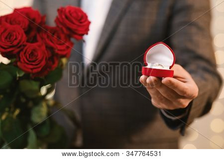 Proposal Concept. Unrecognizable Man Holding Box With Diamond Ring And Roses Bouquet, Proposing To M