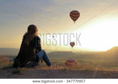 Woman Looking At Air Baloons Flying At Sunrise In Cappadocia