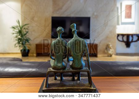 Man And Woman Couple Statuette Watching Tv In Living Room