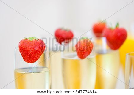 Glasses Of Sparkling Wine Or Champagne And Strawberry On A Blurry Background During Some Sort Of Fes