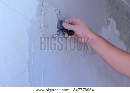 Plasterer Man Is Spackling Wall With Putty Plaster Aligning Wall, Hand Closeup. Finishing Constructi