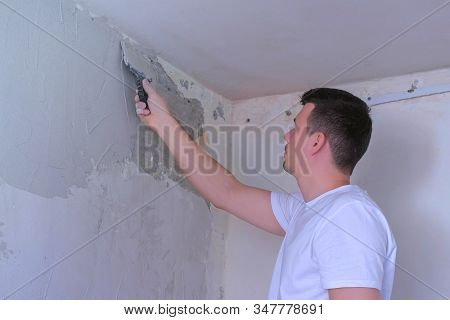 Plasterer Man Spackling Wall With Putty Plaster Aligning Wall With Spatula. Finishing Construction R