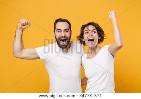 Joyful Young Couple Friends Bearded Guy Girl In White Empty Blank T-shirts Posing Isolated On Yellow