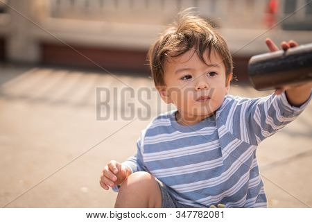 Cute Young Boy Playing At The Playgound Alone And Have A Happy Time