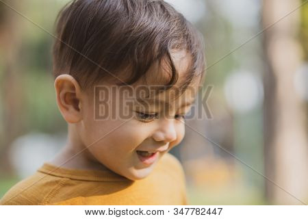 Happy Young Boy Playing Outdoors In The Park