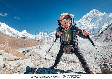 Portrait Of Smiling Hiker Man With Nuptse 7861 M Peak And Gorak Shep Settlement Background With Trek