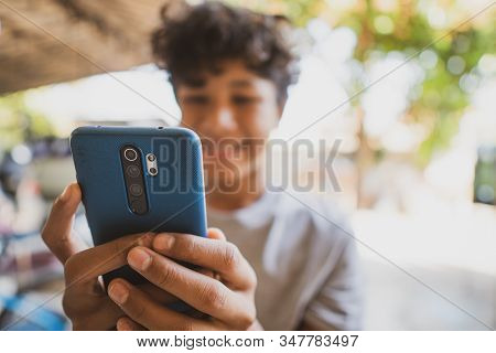 Asian Boy Smailing And Playing On Cell Phone